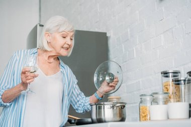 side view of senior lady with glass of wine checking saucepan on stove in kitchen