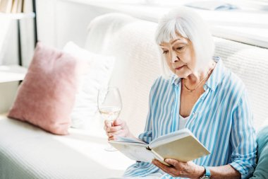focused senior woman with glass of wine reading book on couch at home