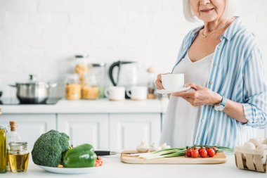 cropped shot of senior woman with cup of coffee standing at counter with fresh vegetables for dinner in kitchen