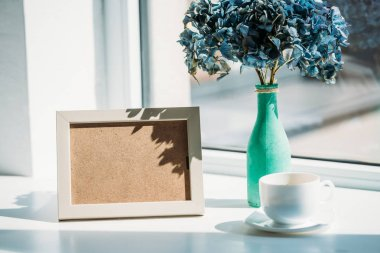 close up view of empty photo frame, cup of coffee and bouquet of hortensia flowers in vase on windowsill