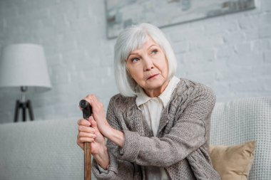 portrait of pensive grey hair lady with wooden walking stick looking away while resting on sofa at home