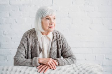 portrait of grey hair lady in knitted jacket leaning on couch and looking away at home