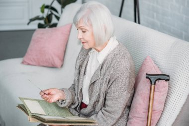 side view of senior lady with photo album resting on couch at home