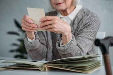 partial view of senior woman looking at photo from photo album at table at home