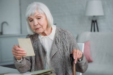 portrait of grey hair woman looking at photo from photo album at table at home