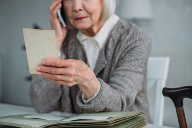 partial view of senior woman with photograph in hand talking on smartphone at home