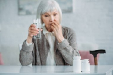 selective focus of grey hair woman with glass of water taking medicine at home