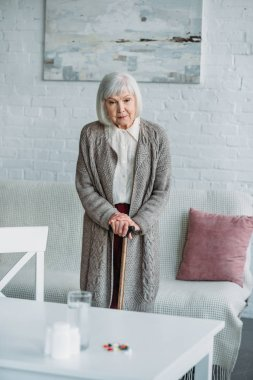 grey hair woman with walking stick standing in room with medicines on tabletop at home