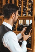 Fotografie handsome young sommelier taking bottle from shelf at wine store