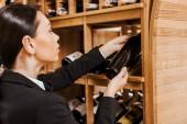 Fotografie atraktivní žena sommeliery pořizování láhev z poličky ve vinotéce
