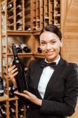 Krásné ženské číšník drží láhev vína v obchodě