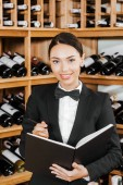 beautiful female wine steward with notebook at wine store