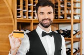 Fotografie smiling young wine steward holding golden card at wine store