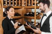 Fotografie několik mladých správci víno dělá inventuru vína