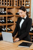 beautiful female wine steward working with laptop at wine store