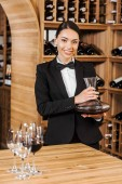 smiling female wine steward holding decanter at wine store