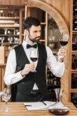 Fotografie confident young sommelier examining color of wine at wine store