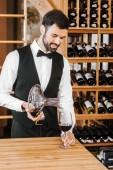 Fotografie pohledný mladý sommelier nalil víno z karafy vína v obchodě