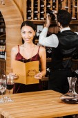 smiling woman holding menu card at wine store while steward taking bottle from shelf on background