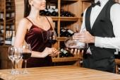 Fotografie oříznuté záběr sommeliery drží karafy vína u ženy klienta ve vinotéce