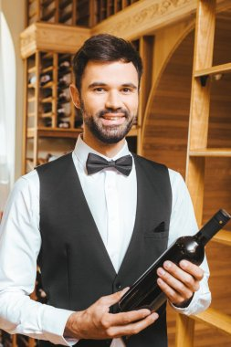 smiling young wine steward with bottle of luxury wine at wine store