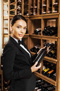 beautiful female wine steward holding bottle and looking at camera at wine store