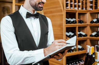 cropped shot of smiling young wine steward making notes at wine store