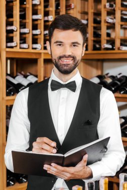 handsome young wine steward making notes and looking at camera at wine store