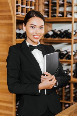 smiling female wine steward witn notebook looking at camera at wine store