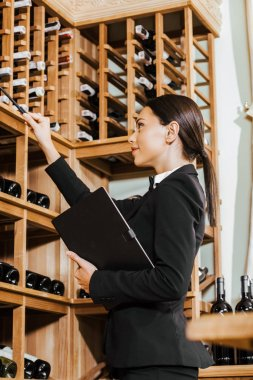 beautiful female wine steward with notebook counting bottles on shelves at wine store