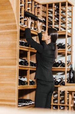 beautiful female wine steward taking bottle from shelf at wine store