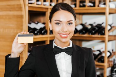 beautiful female wine steward with golden credit card at wine store