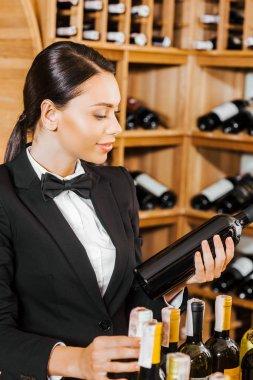 attractive female wine steward with wine bottles at wine store
