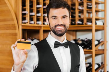smiling young wine steward holding golden card at wine store