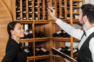 couple of wine stewards doing stocktaking of wine on shelves at store