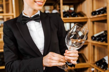 cropped shot of female wine steward with clean glass at wine store