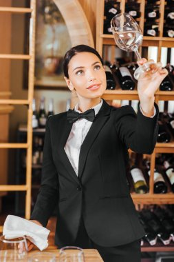 beautiful female wine steward checking clear glass at wine store