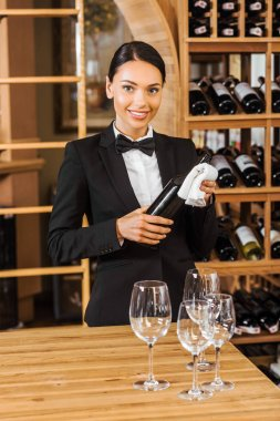 smiling female wine steward holding bottle at wine store