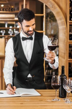 smiling young sommelier examining color of wine and making notes at wine store