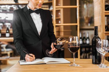 cropped shot of female wine steward looking at glass of wine and writing in notebook at wine store