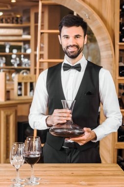 handsome young sommelier holding decanter of red wine at wine store