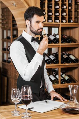 handsome young wine steward examining aromatic bottle corc after opening wine at store