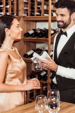 wine steward showing bottle of luxury wine to female client at wine store