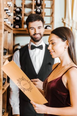smiling woman holding menu card at wine store while steward standing blurred on background