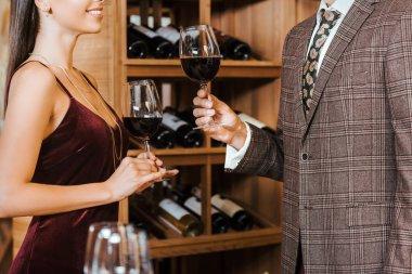 cropped shot of elegant couple toasting with wine glasses at wine storage
