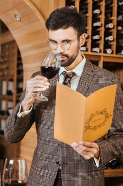 handsome young sommelier with menu card sniffing wine from glass at wine store