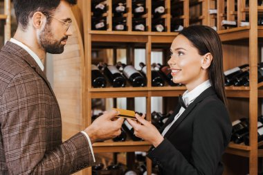female wine steward taking credit card from customer at wine store