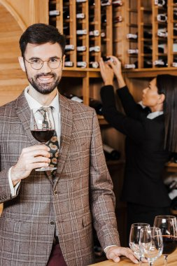 female wine steward taking bottle from shelf for client while he looking at camera at wine store