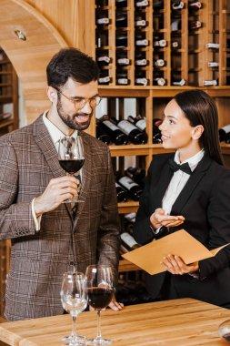 female wine steward showing menu list to client at wine store