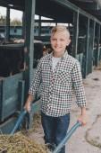 Fotografia ragazzo che spinge la carriola con erba e sorride alla macchina fotografica nella stalla